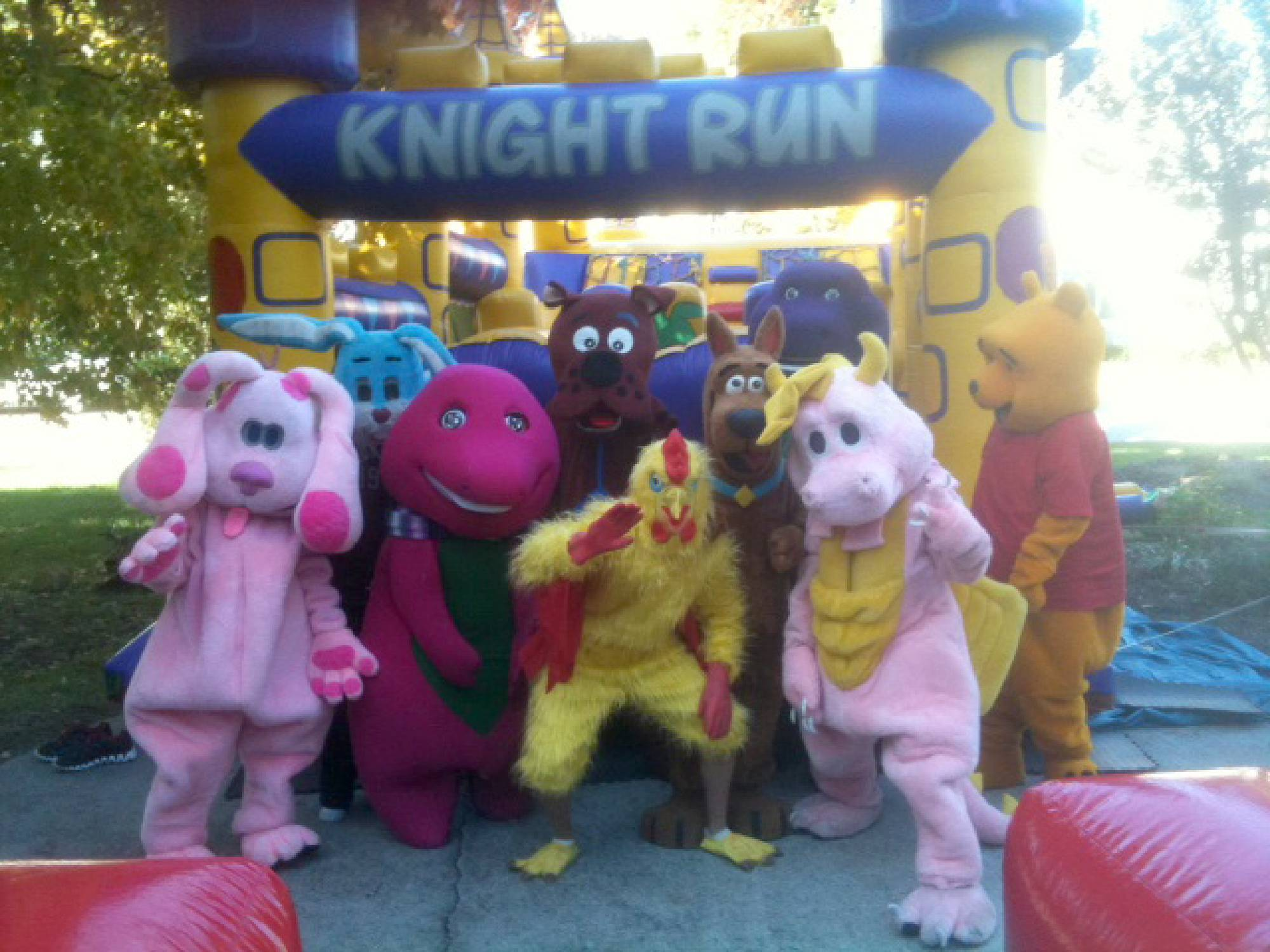 Costumed characters in front of obstacle course rental in Raleigh